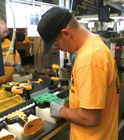 A DeWalt assembly team member uses a green Poka Yoke jig to guide screw placement as he builds a cordless drill.